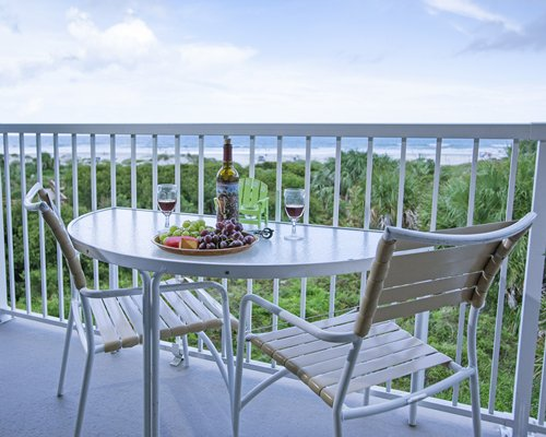 Patio furniture on the balcony facing the ocean.