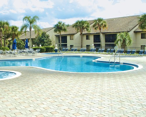 An outdoor swimming pool and hot tub with chaise lounge chairs and patio tables with umbrellas.