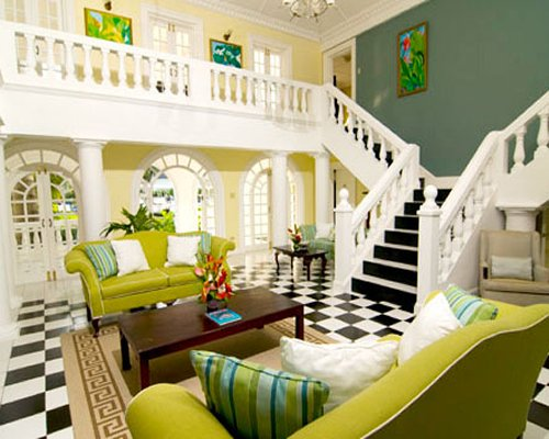 A well furnished living room with stairway and indoor balcony.