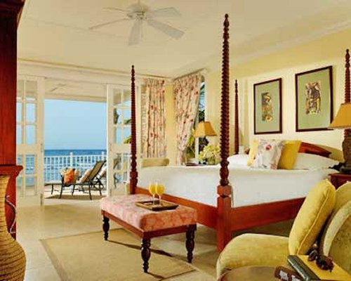A well furnished bedroom with king bed facing the ocean.