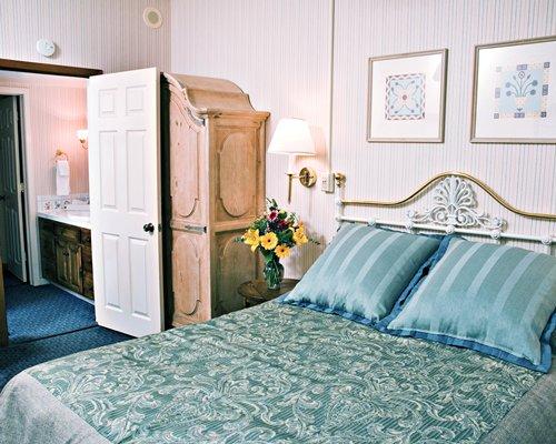A well furnished bedroom alongside a bathroom.