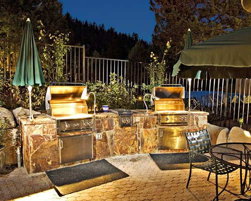 An outdoor area with barbecue grills and patio furniture.