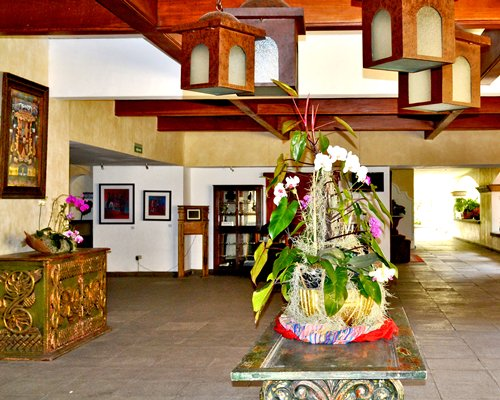 A reception area of the resort with an assorted flower showpiece in the middle.