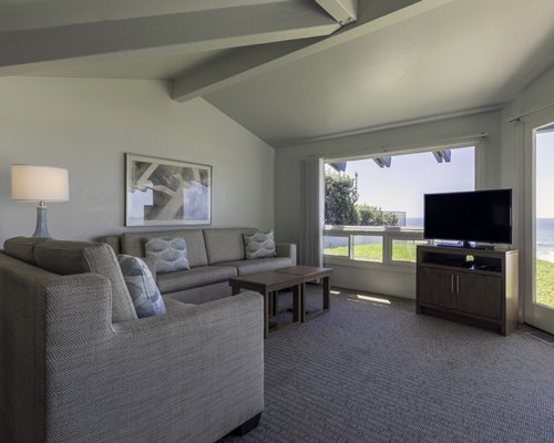 A well furnished living room with a television and an outdoor view.