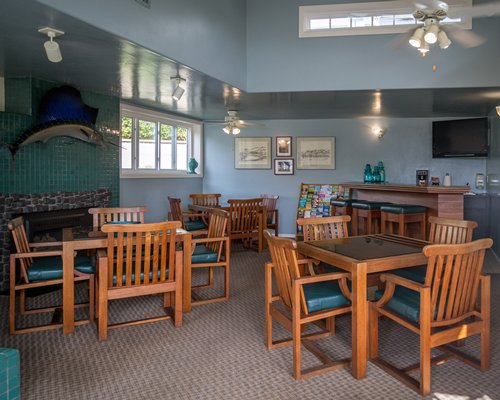 A large indoor dining area with multiple tables and television.