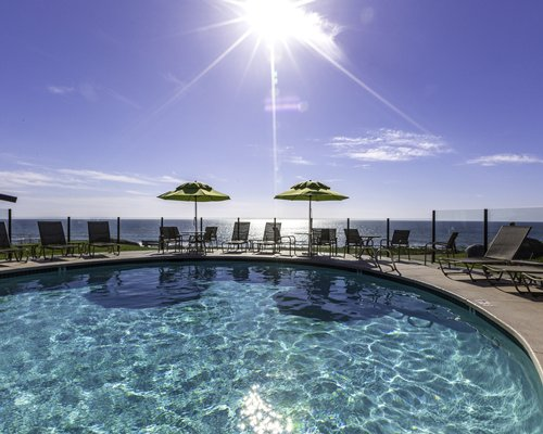 An outdoor swimming pool with chaise lounge chairs and sunshades alongside ocean.