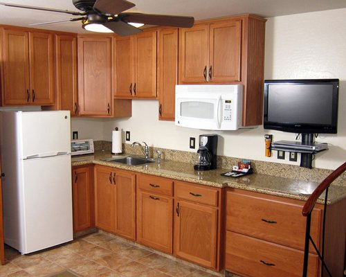 A well equipped modular kitchen with a television.