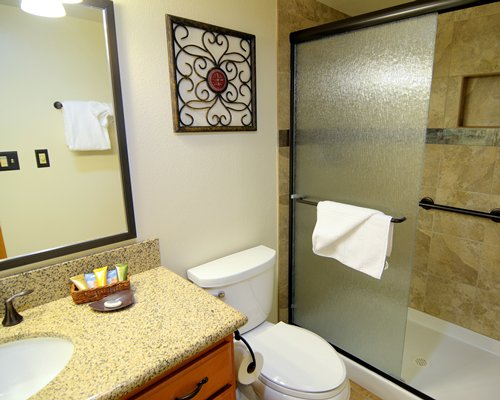 A bathroom with stand up shower sink and mirror.