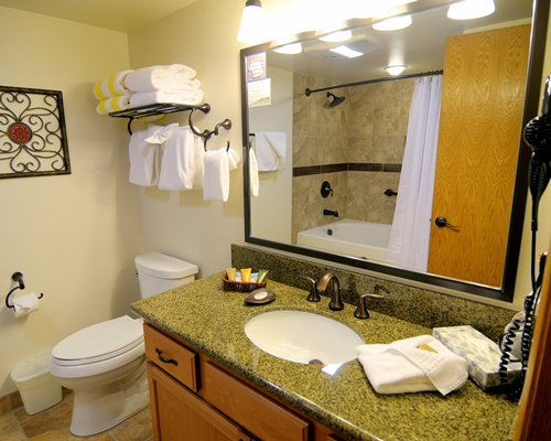 A bathroom with bathtub shower and single sink vanity enclosed toilet.