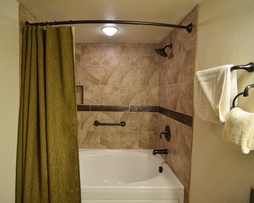 A bathroom with bath tub and stand up shower.