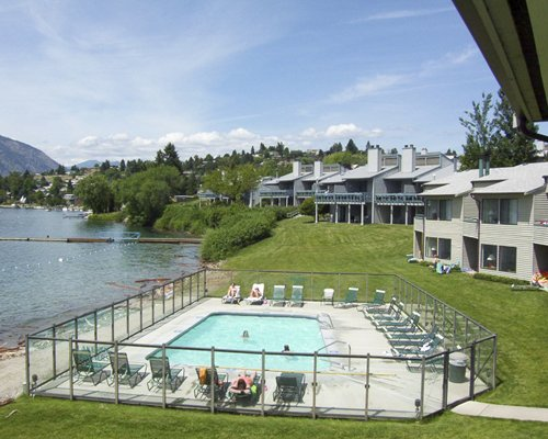 An outdoor swimming pool with chaise lounge chairs alongside resort and the lake.