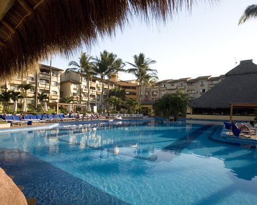 An outdoor swimming pool alongside the resort and a poolside bar.