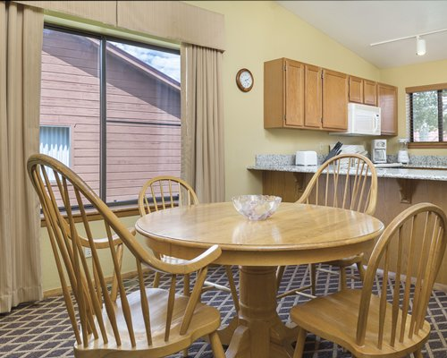 A well furnished dining area alongside the kitchen with an outside view.