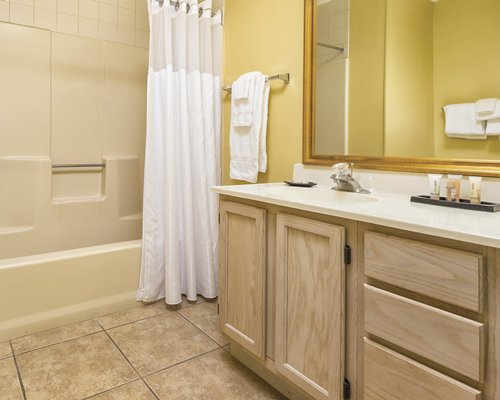 A bathroom with shower bathtub and closed vanity sink.