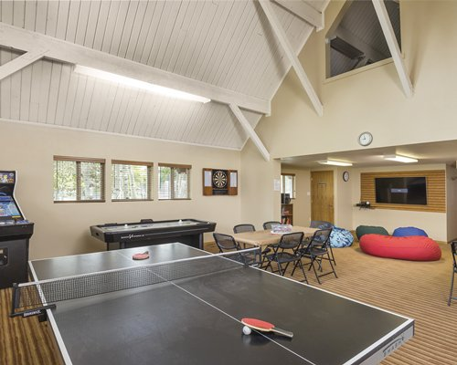 An indoor recreation room with an arcade game ping pong and pool table.
