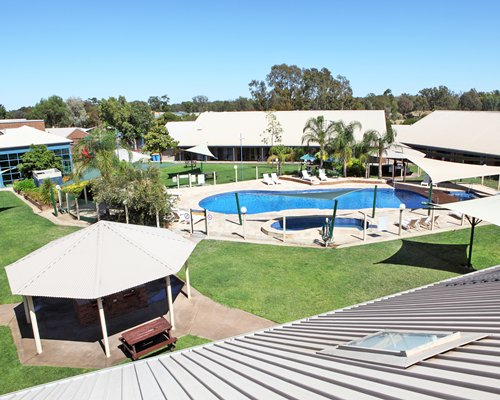 Balcony view of an outdoor swimming pool alongside resort units.