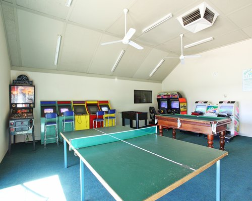 An indoor recreation room with ping pong pool table and arcade games.