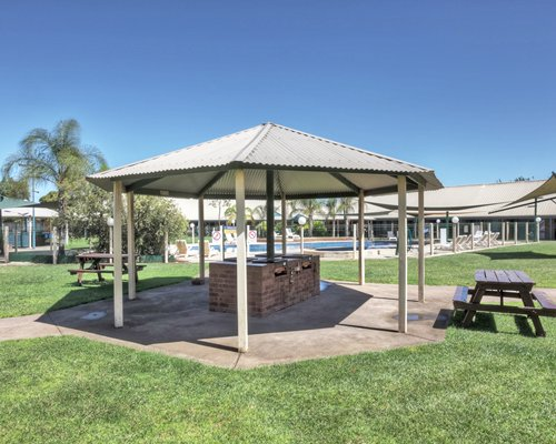 Outdoor picnic area with covered barbecue grills and wooden bench.