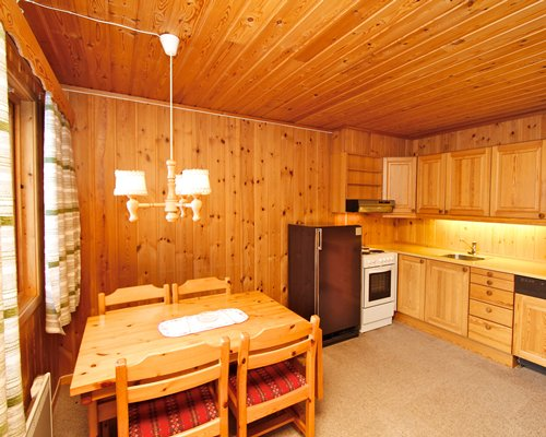 A wood paneled kitchen with a dining area.