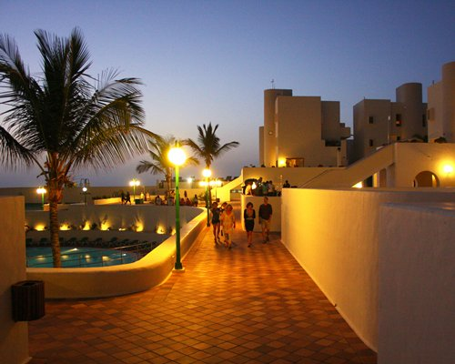 Night view of a pathway alongside the swimming pool and the resort.