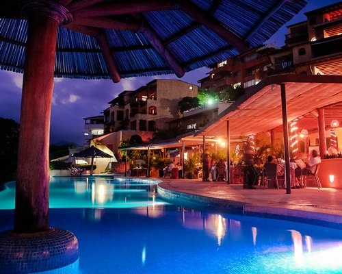 Night view of an outdoor swimming pool with thatched sunshade alongside a dining area.