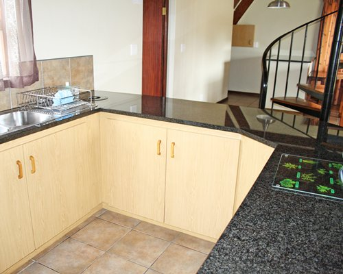 A well equipped kitchen with the curved staircase.