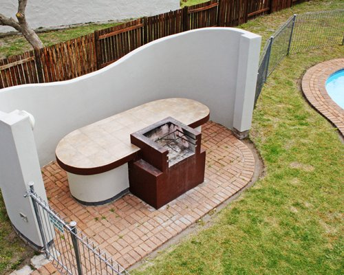 An outdoor barbecue grill alongside swimming pool.