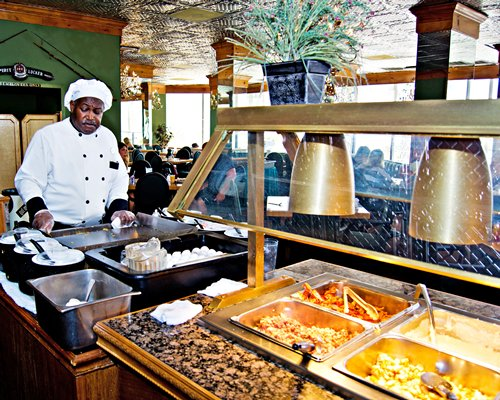 A chef at an indoor restaurant with buffet.