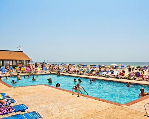 View of people at an outdoor swimming pool with chaise lounge chairs and sunshades alongside the ocean.
