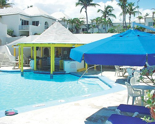 An outdoor swimming pool with sunshades patio furniture and chaise lounge chairs alongside the resort.