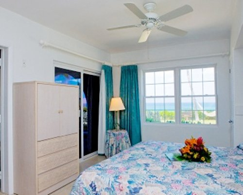 A well furnished bedroom with king bed and ocean view.