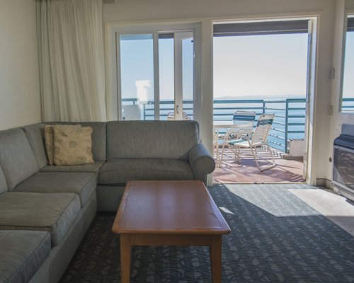 A well furnished living room with patio furniture in the balcony.