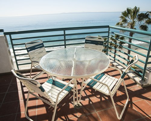 A view of patio furniture in the balcony alongside the ocean.