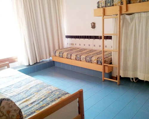 A well furnished bedroom with bunk beds and outside view.