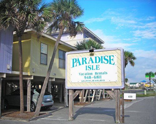 Signboard and exterior view of a pathway to Paradise Isle Resort with palm trees.