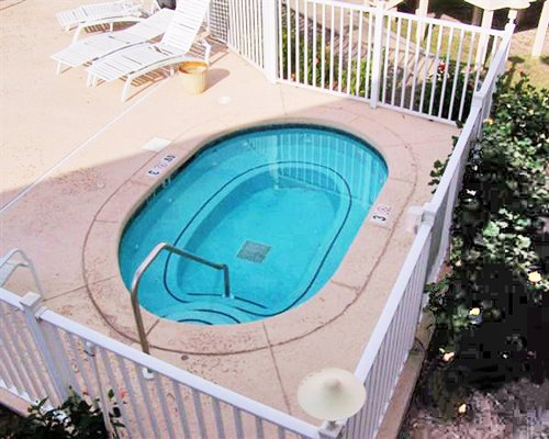 An aerial view of a hot tub alongside the chaise lounge chairs.