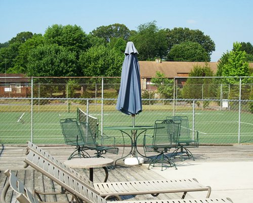 A view of chaise lounge chairs and patio furniture alongside outdoor tennis court.