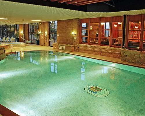 An indoor swimming pool with hot tub alongside chaise lounge chairs.