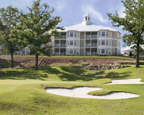 Scenic resort exterior view of multiple unit balconies overlooking golf greens.