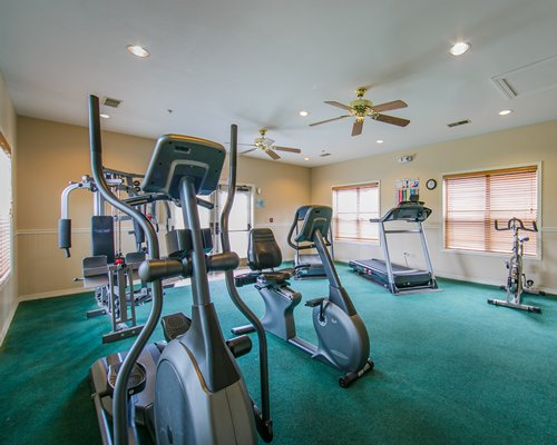 A gym with equipment and windows.