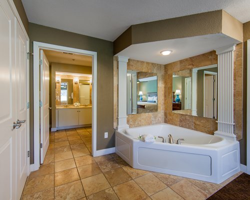 A view of large bathroom with a corner bathtub.