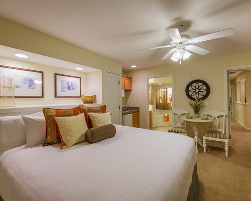 A well furnished bedroom with a large bed table seating and bathroom door view.