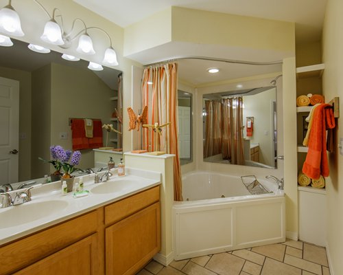 A large bathroom with a corner bathtub and double sink vanity.