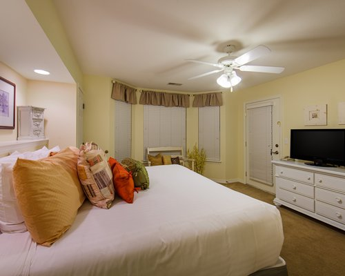 A well furnished bedroom with a large bed and television.