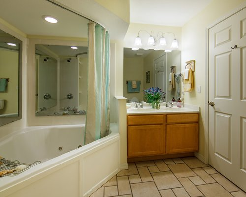 A bathroom with a corner bathtub and double sink vanity.