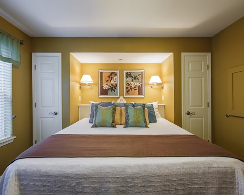 A well furnished bedroom with a large alcove bed and closets.