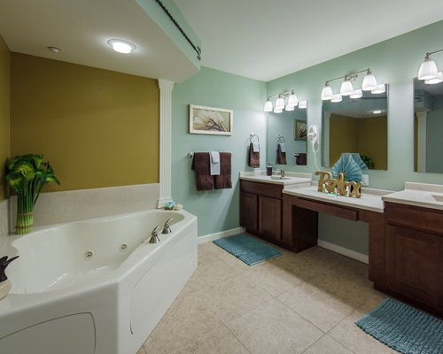 A bathroom with a corner jacuzzi bathtub and double sink vanity.