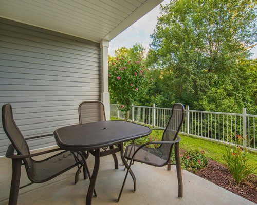 A private patio area with table seating and landscaped yard views.