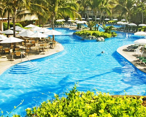 A large landscaped outdoor swimming pool with thatched sunshades.