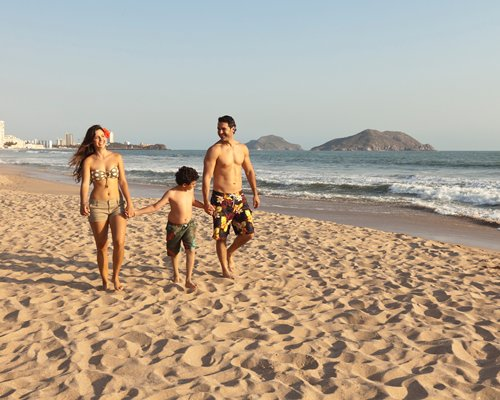 A family walking on the beach alongside the ocean.